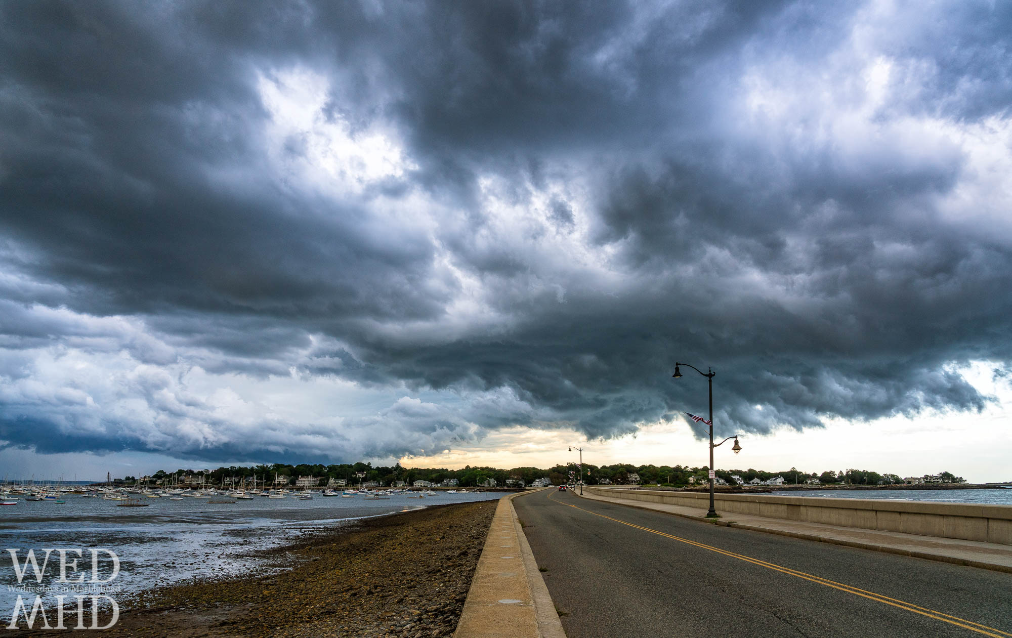 A passing storm crosses over the causeway creating a dramatic sky over Marblehead Neck on a late August evening