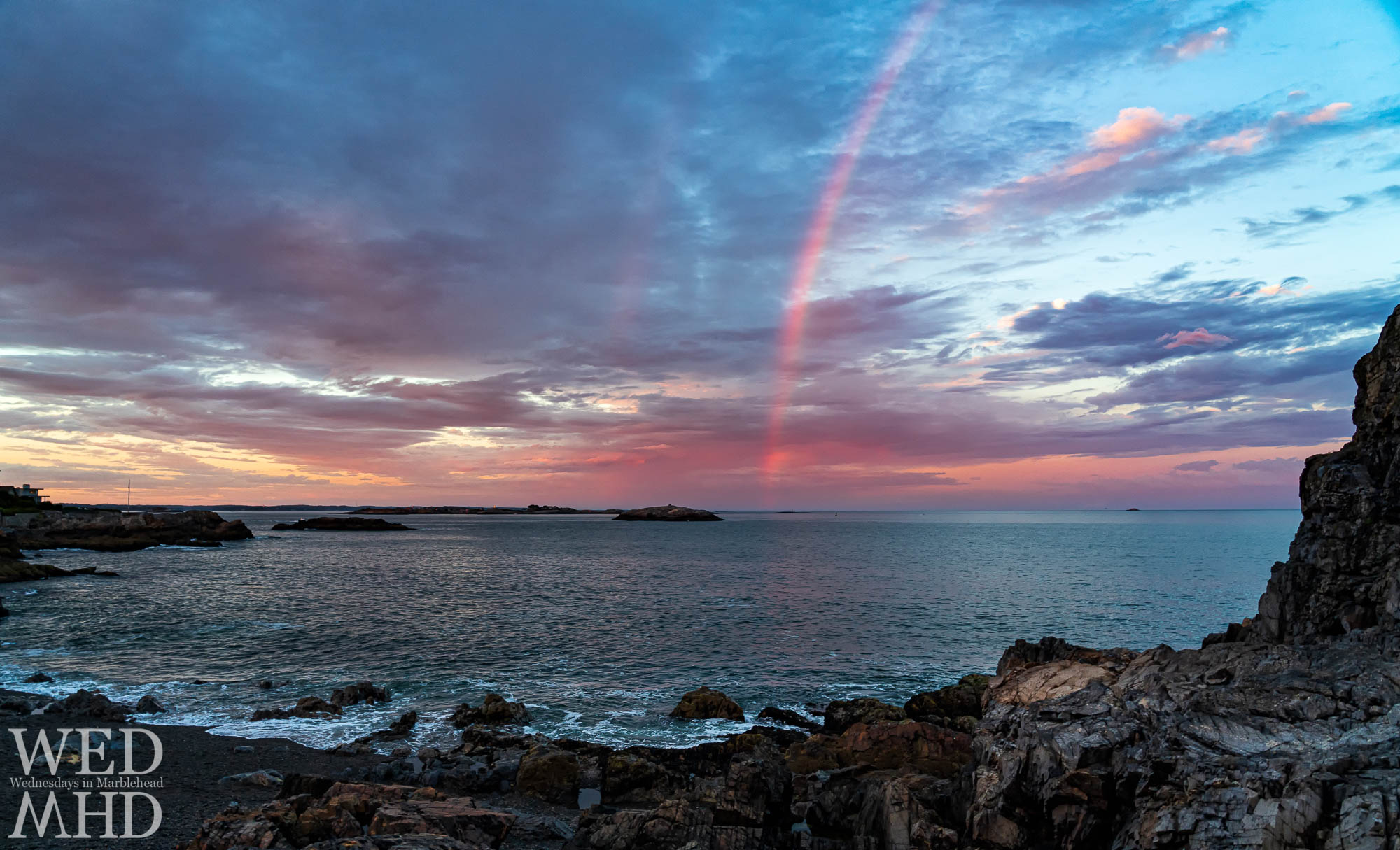 A rainbow forms in the pink sky of sunset over Castle Rock after a summer storm passes by Marblehead