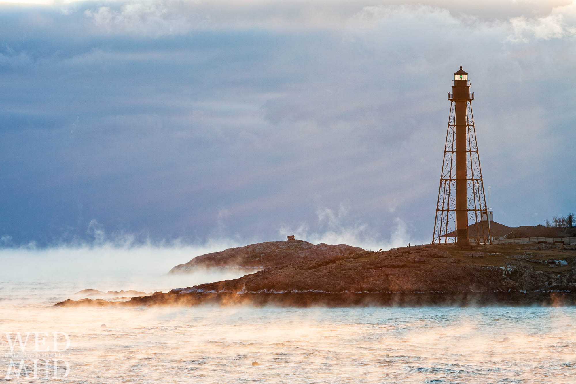 Sea smoke rises from the warm ocean waters and into the frigid air encircling Marblehead Light at dawn