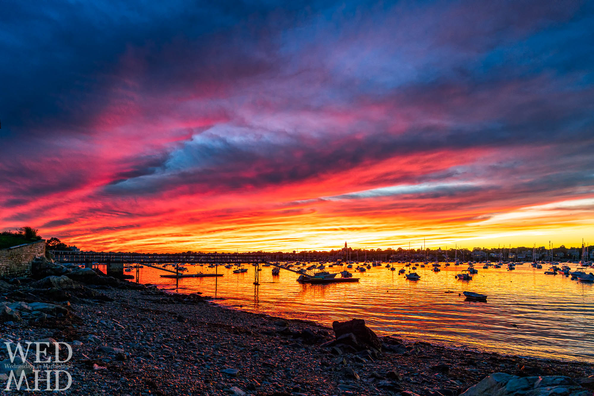 A vibrant September sunset forms over Marblehead harbor as viewed at low tide from the end of Peabody Lane on the Neck