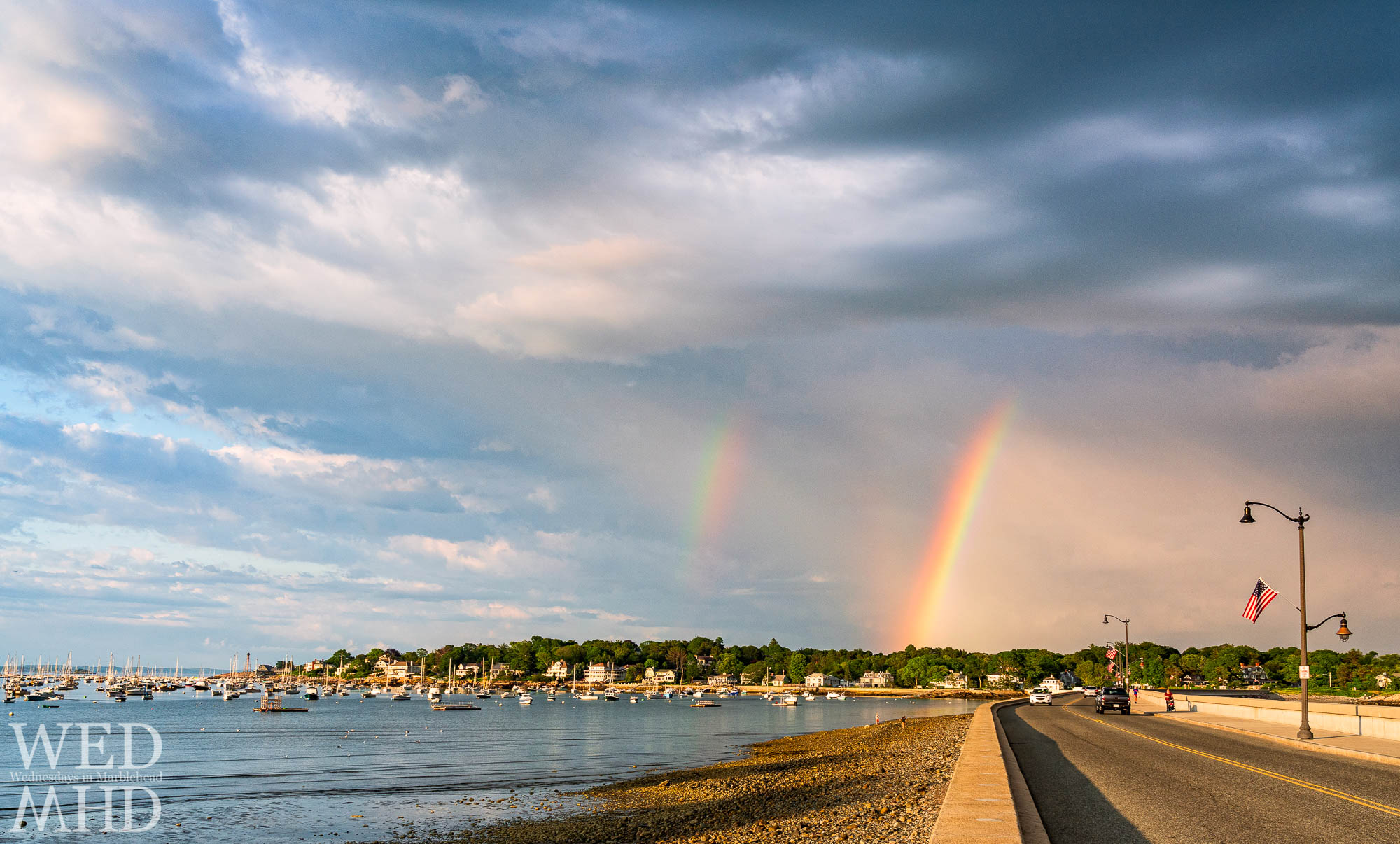 Double summer rainbows shine over the causeway with lamp posts adorned with flags for the upcoming Independence Day