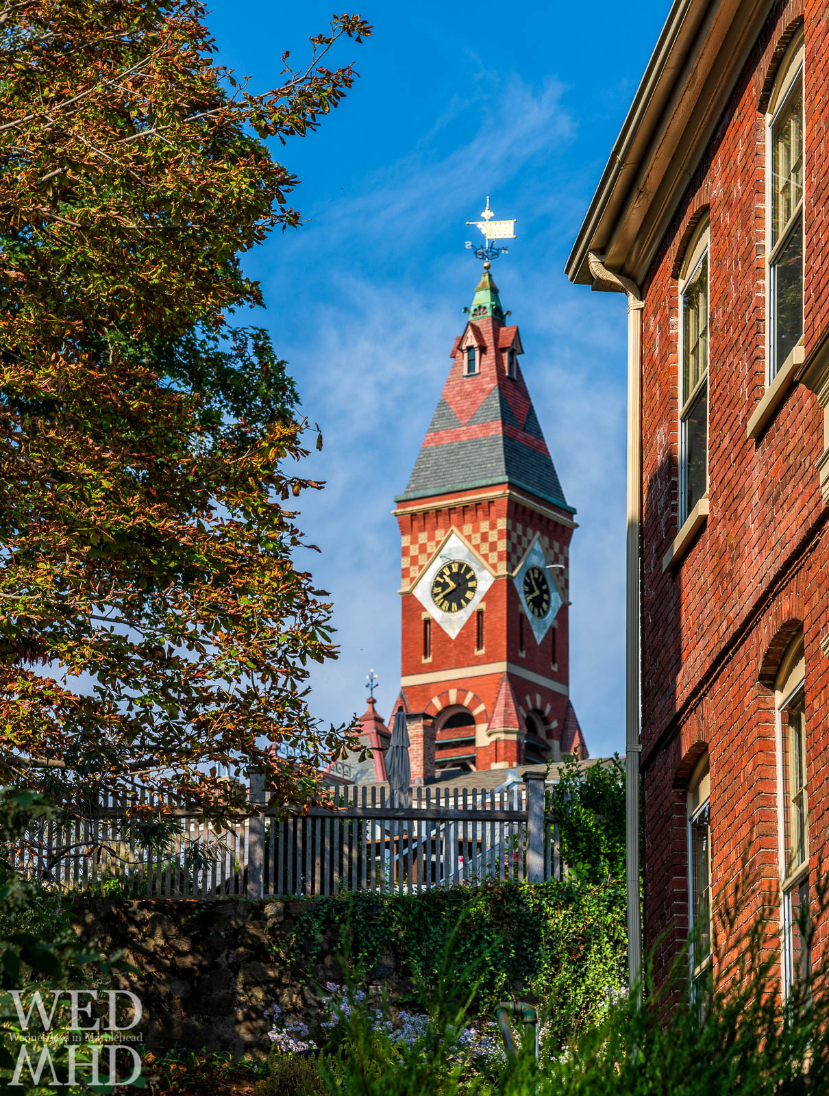 Fall colors and a brick house frame this image of Abbot Hall above Prospect Alley on a crisp autumn day in Marblehead