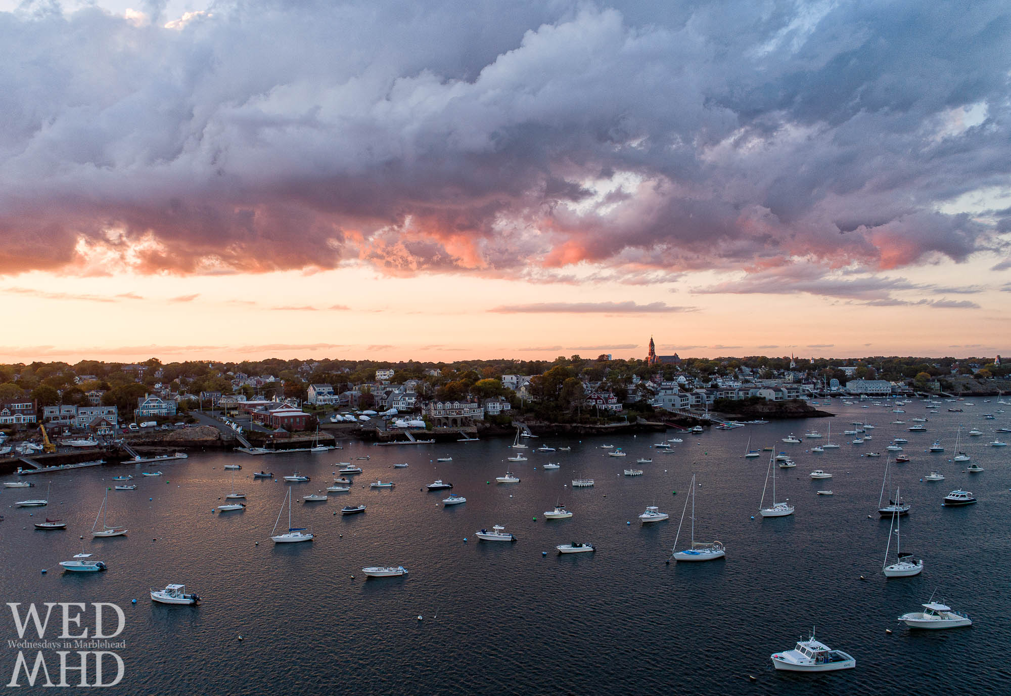 Sunset takes shape on an October sky as seen from the vantage point of an aerial drone capturing the feeling of fall over the harbor
