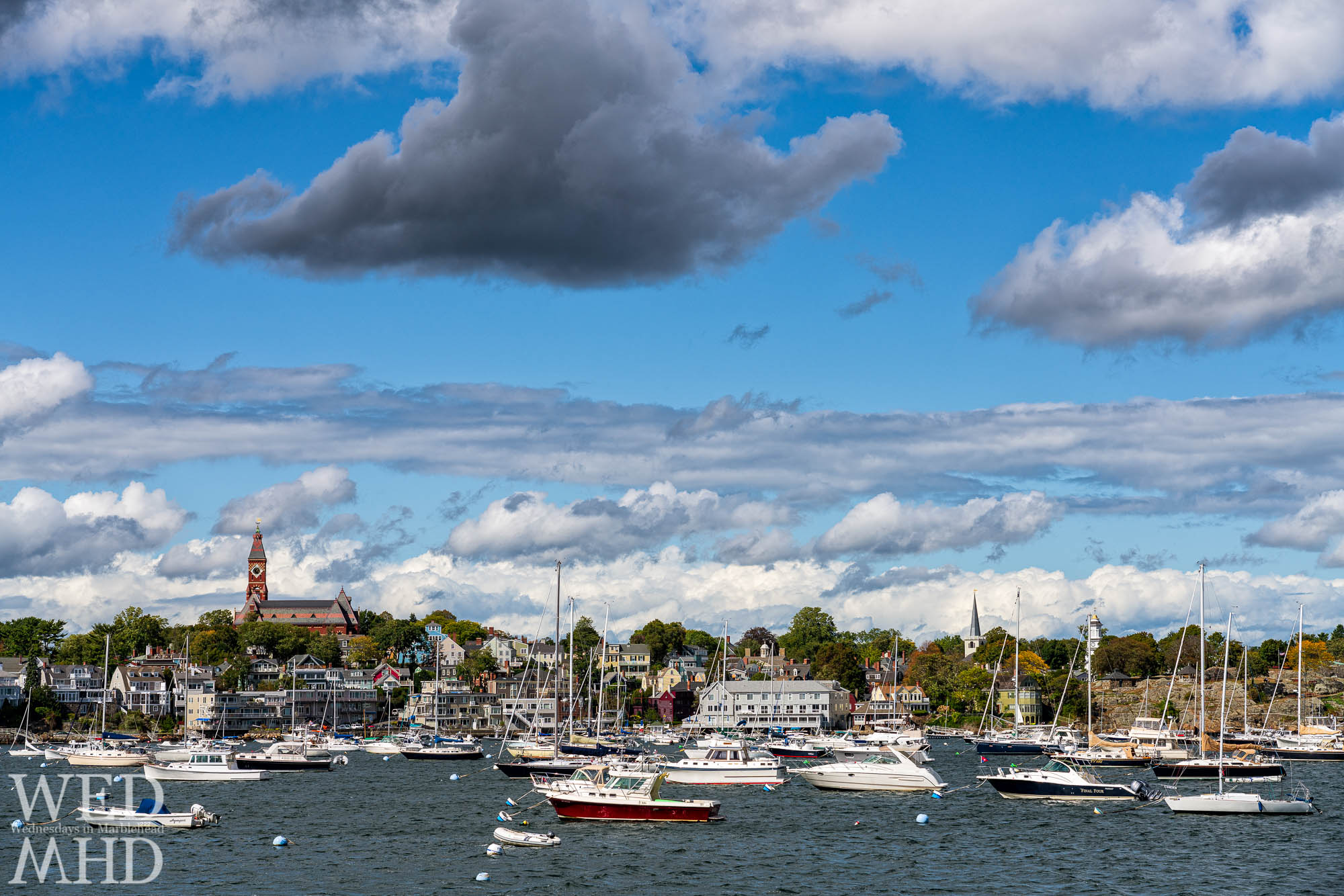 Abbot Hall, St. Michaels and the Grace Community Church form a backdrop to a harbor filled with boats as seen from Parker Lane on the Neck