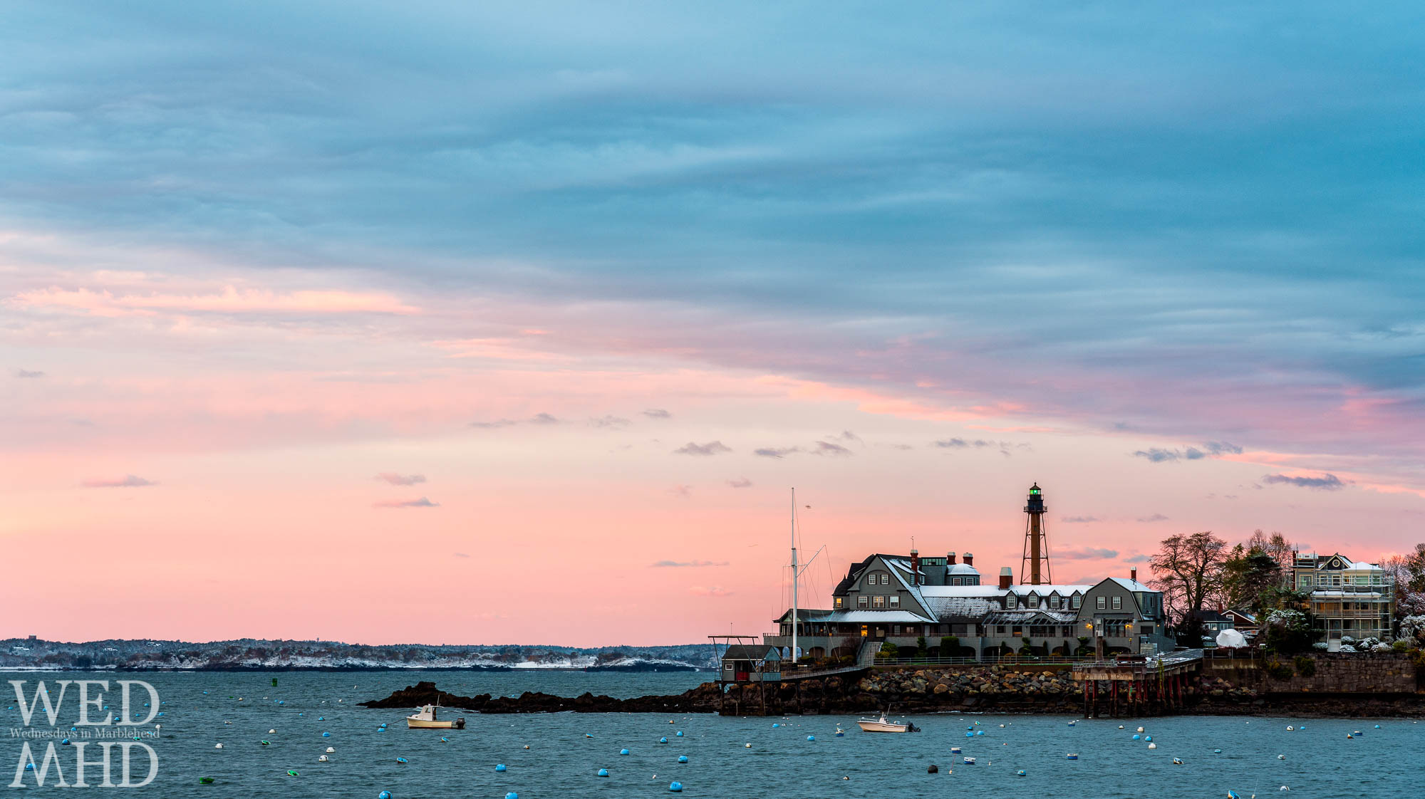A coating of snow created a bit of contrast on the Corinthian Yacht Club with Marblehead Light and its green beacon shining behind it