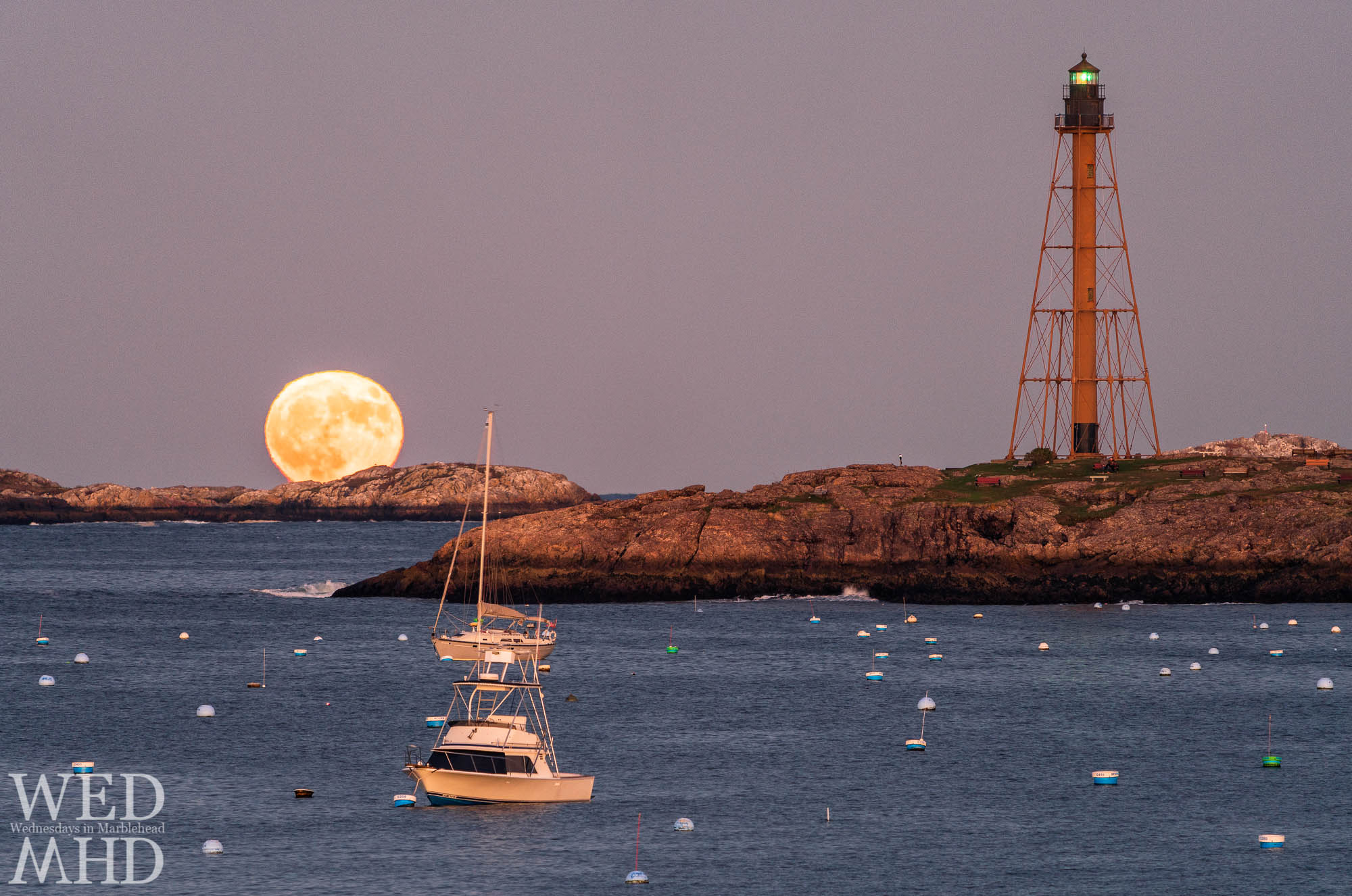 A rare Halloween blue moon rises behind Childrens Island and two boats still moored in the harbor while Marblehead Light's green beacon shines
