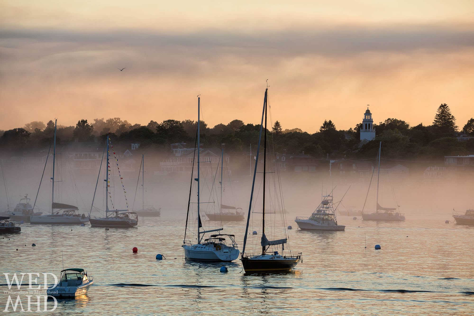 Remembering humid days and foggy nights in Marblehead Harbor with boats moored in front of Old North Church