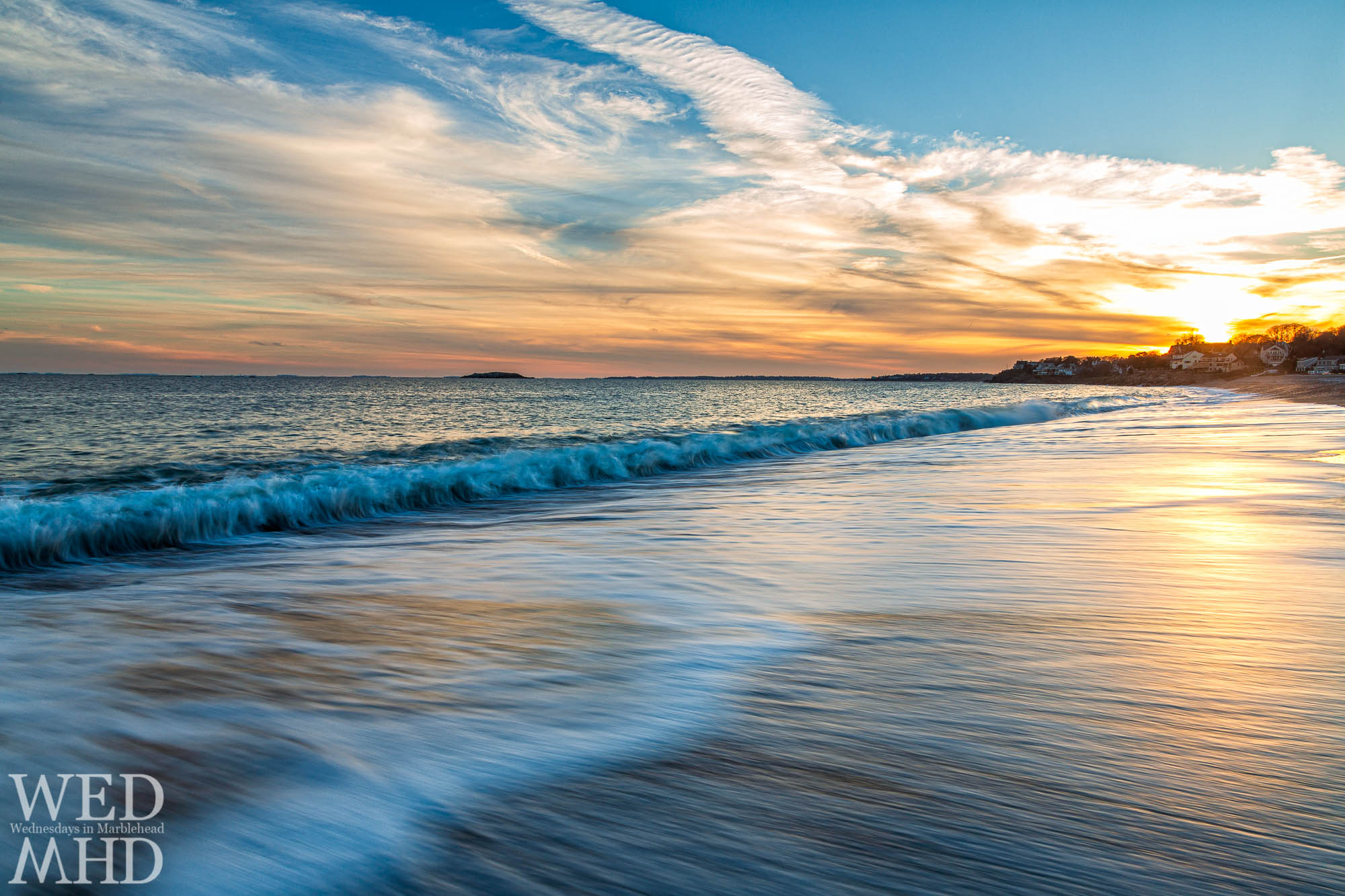 Waves recede from shore and reflect the light of sunset in this long exposure image captured at Devereux Beach