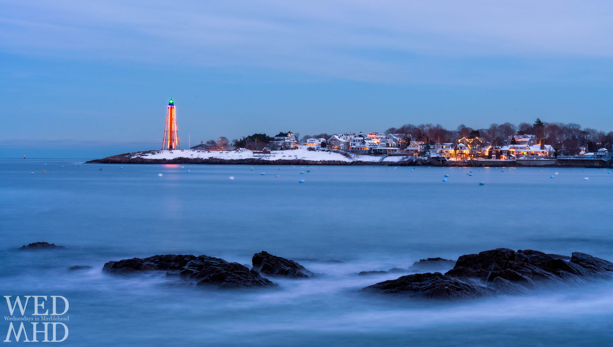 Marblehead Light seen shining bright on the neck with fresh fallen snow contrasting the rocks and a long exposure softening the waves