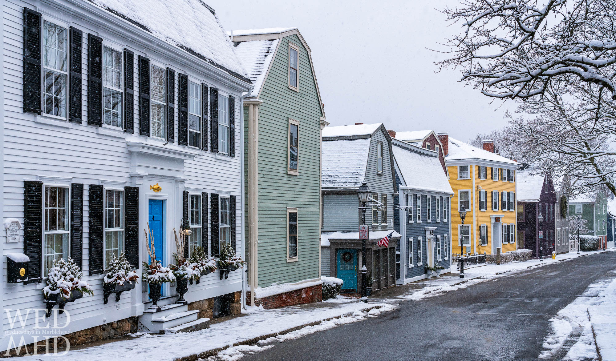 Falling snow coats roofs and sidewalks in white and seems to help the homes on State Street shine brighter on a January morning in Marblehead