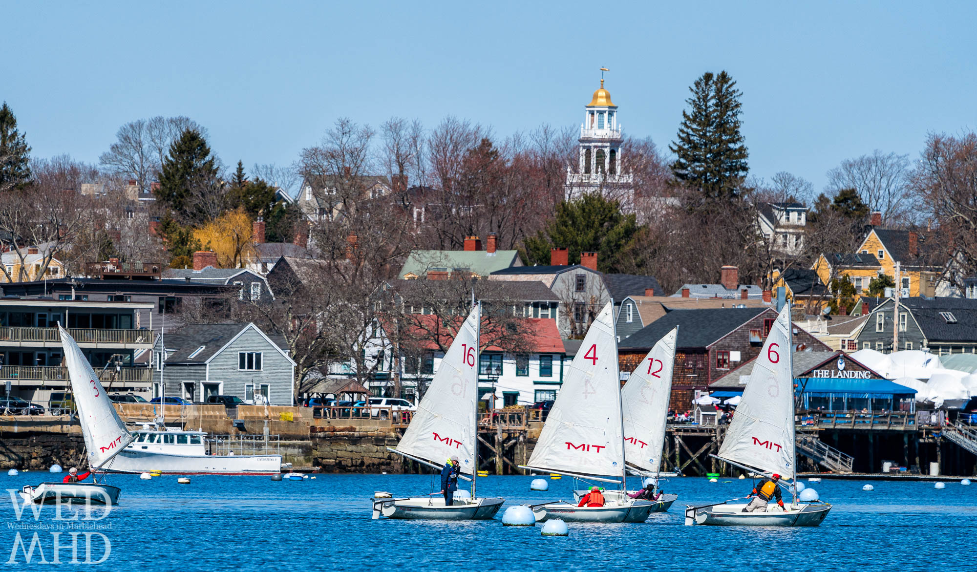 A group is seen passing by The Landing restaurant and Old North Church during the Marblehead Tech Dinghy Association inner harbor race