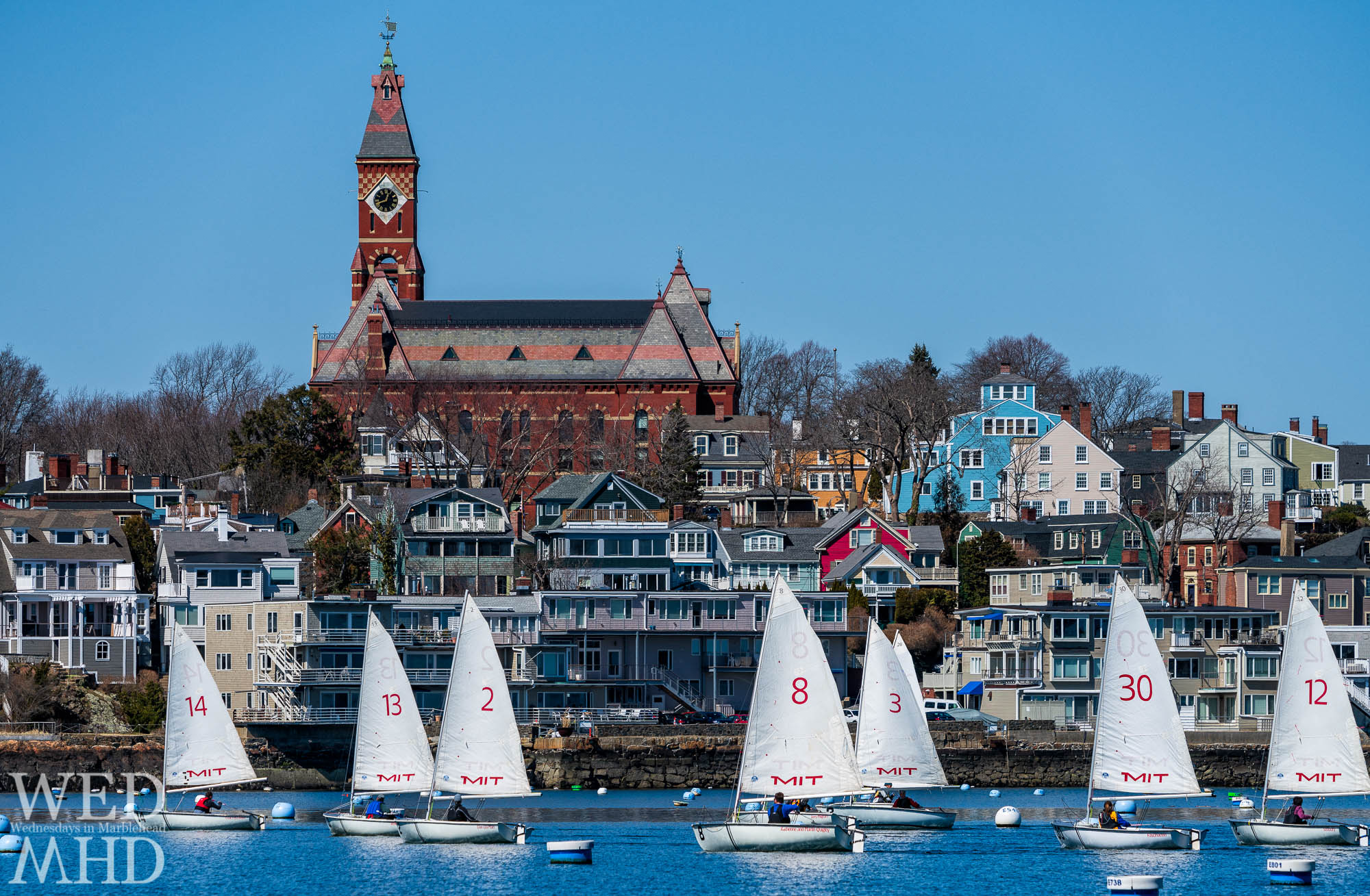 The Marblehead Tech Dinghy Association races in front of Abbot Hall. Spring was in the air and, with the MIT on the sails, it seems class is in session in Marblehead.