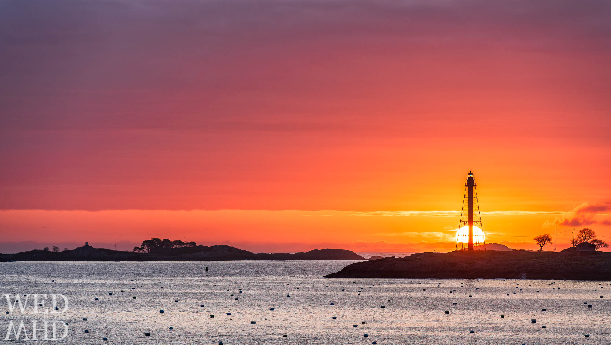 The sun rises behind Marblehead Light and Chandler Hovey Park with Childrens Island visible in the morning glow
