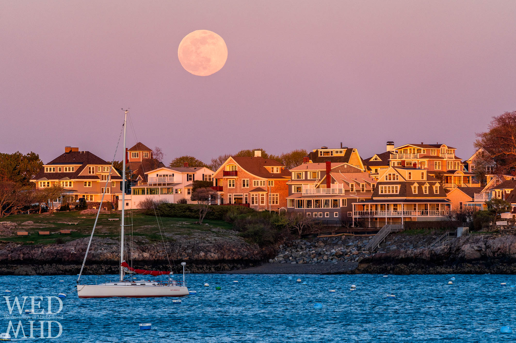The full pink moonrise over houses on the Neck bathed in golden light from the setting sun with a lone sailboat moored in the harbor