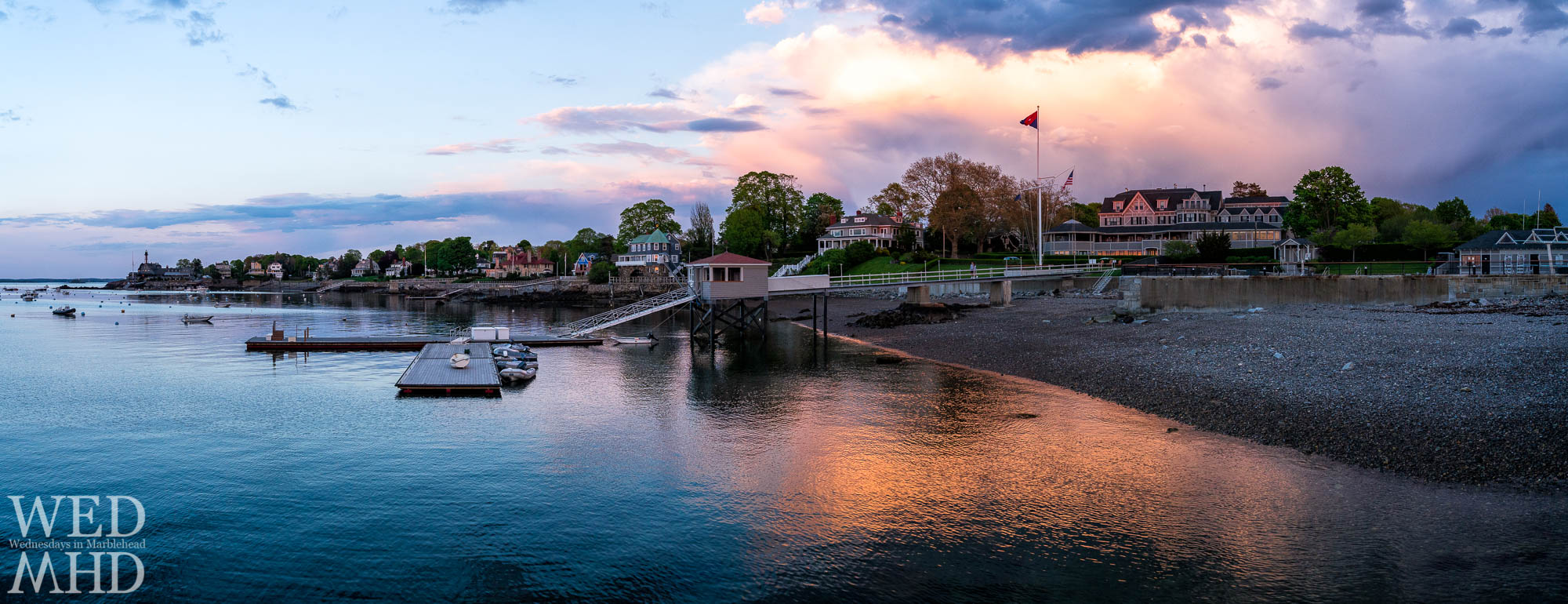 The Eastern Yacht Club set aglow in evening light with sunset lighting up the clouds above and reflected in the waters of the harbor