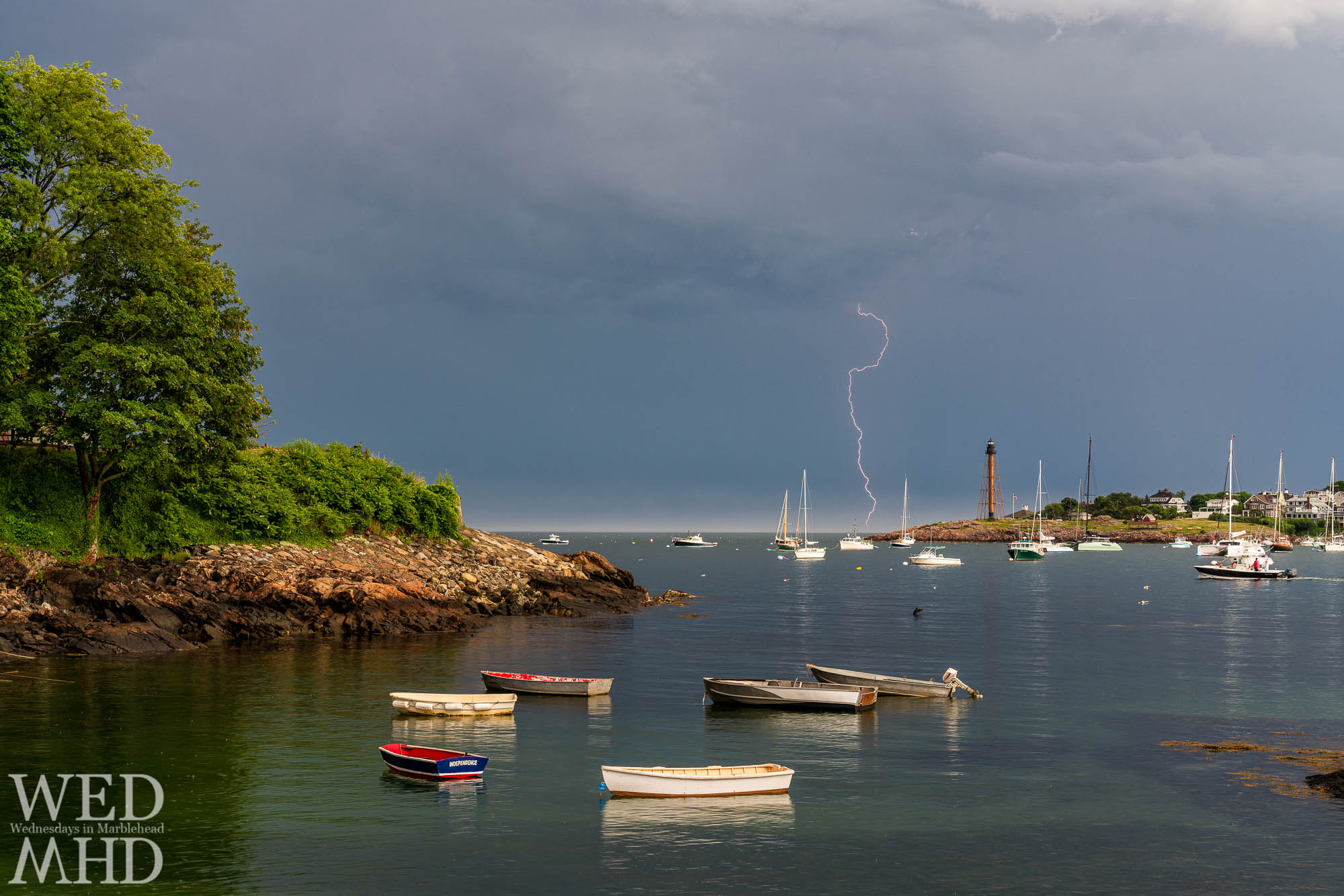 Lightning crashes besides Marblehead Light as a summer heat wave breaks with a night of storms