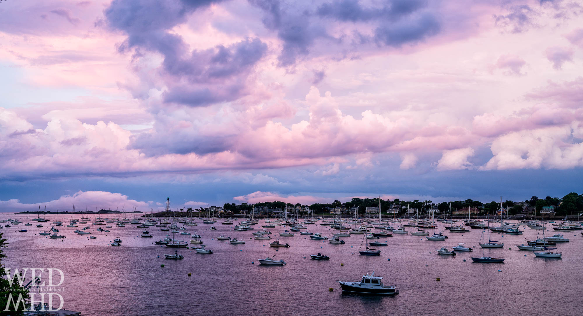 The last light of a great sunset creates a purple afterglow over Marblehead Harbor with the lighthouse's green beacon shining through