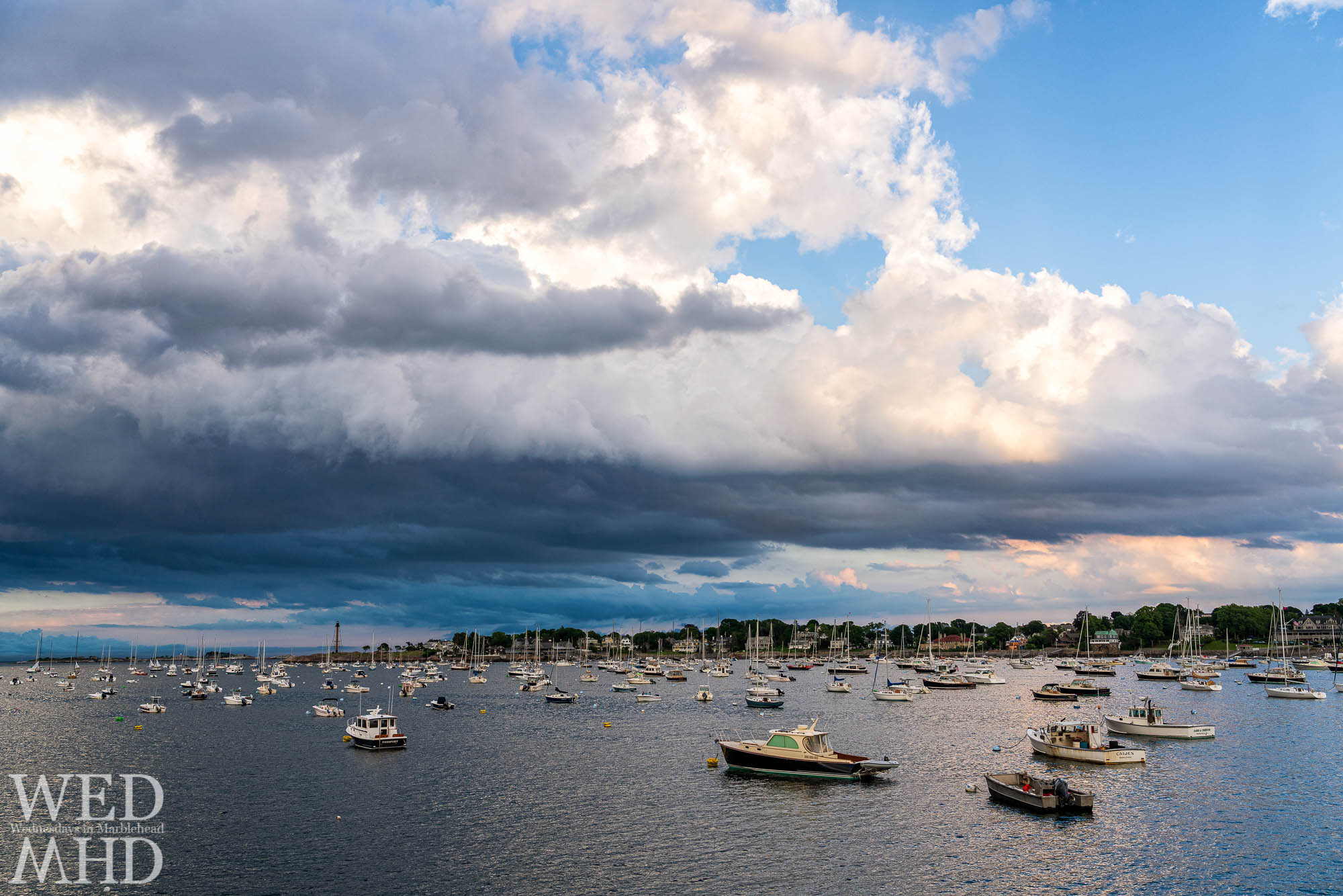 Storm clouds gather with boats in their moorings pointing toward the interesting sky as the show is about to begin