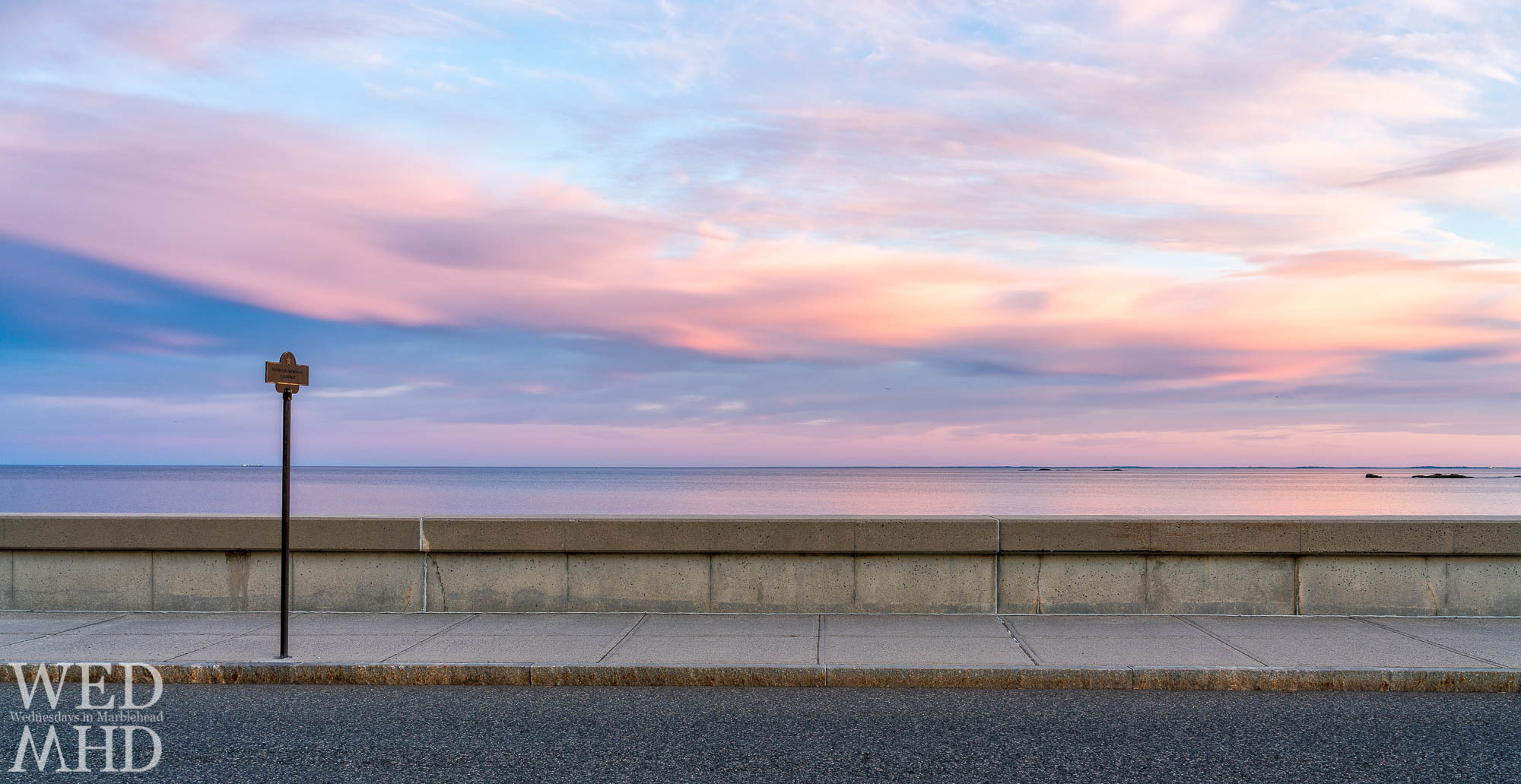 The Veterans Memorial Causeway is captured at sunset with a soft display of color reflecting on the calm water of the Atlantic ocean
