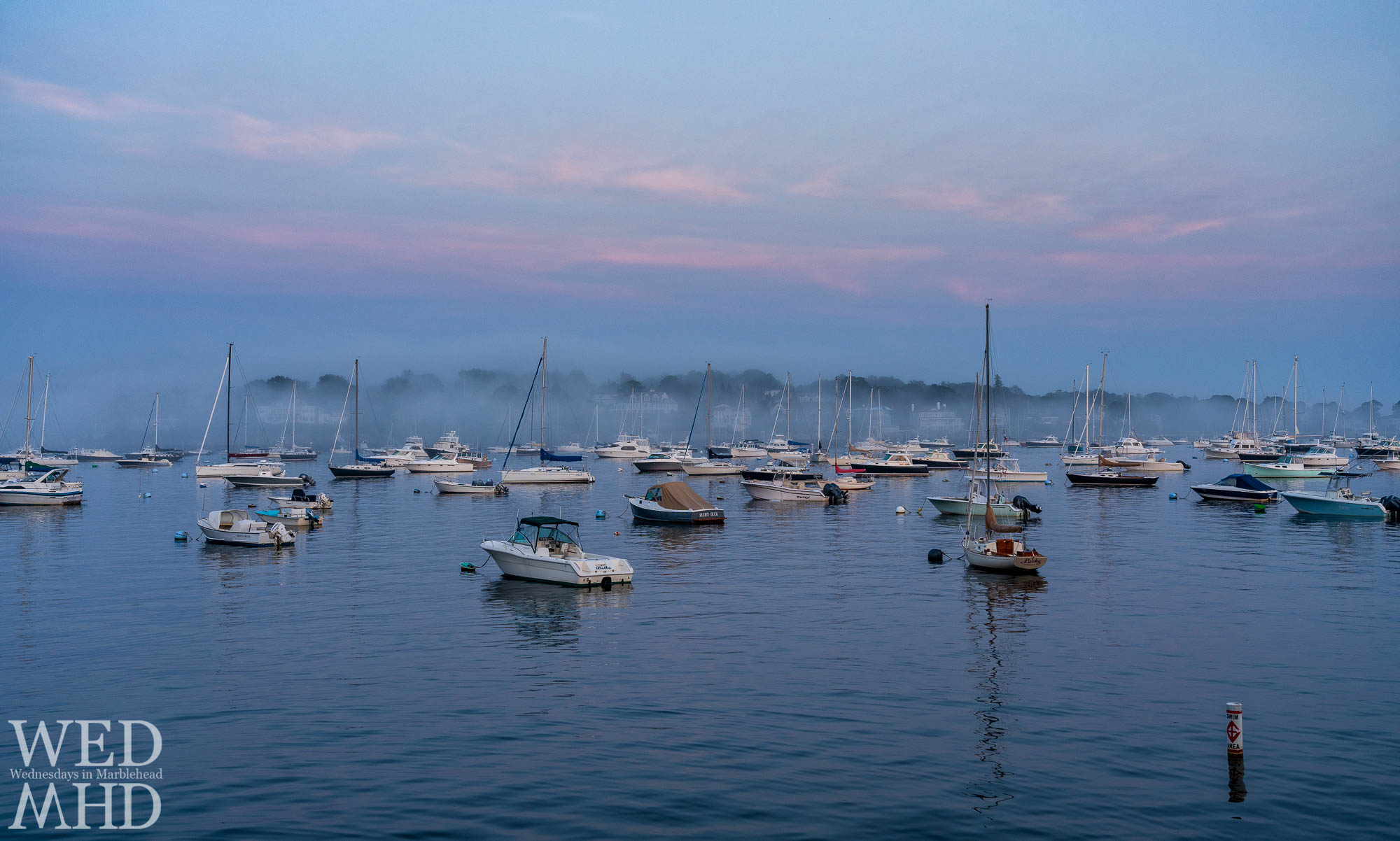 Soft pink light creates a foggy sunset over the harbor and Marblehead Neck on a July filled with rainy days