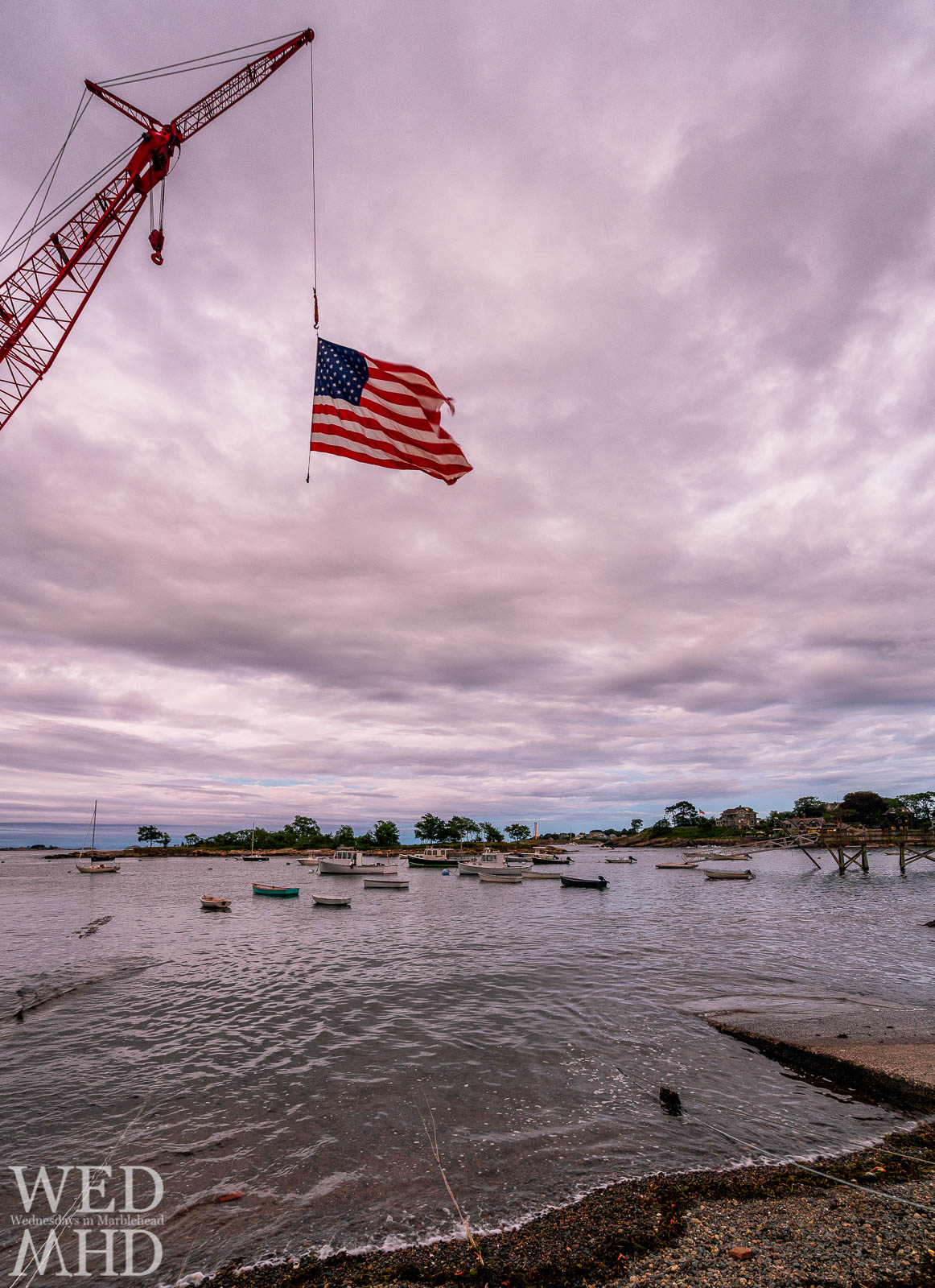 Old glory flies from the crane at Little Harbor with boats filling the protected waters and Marblehead Light in the distance
