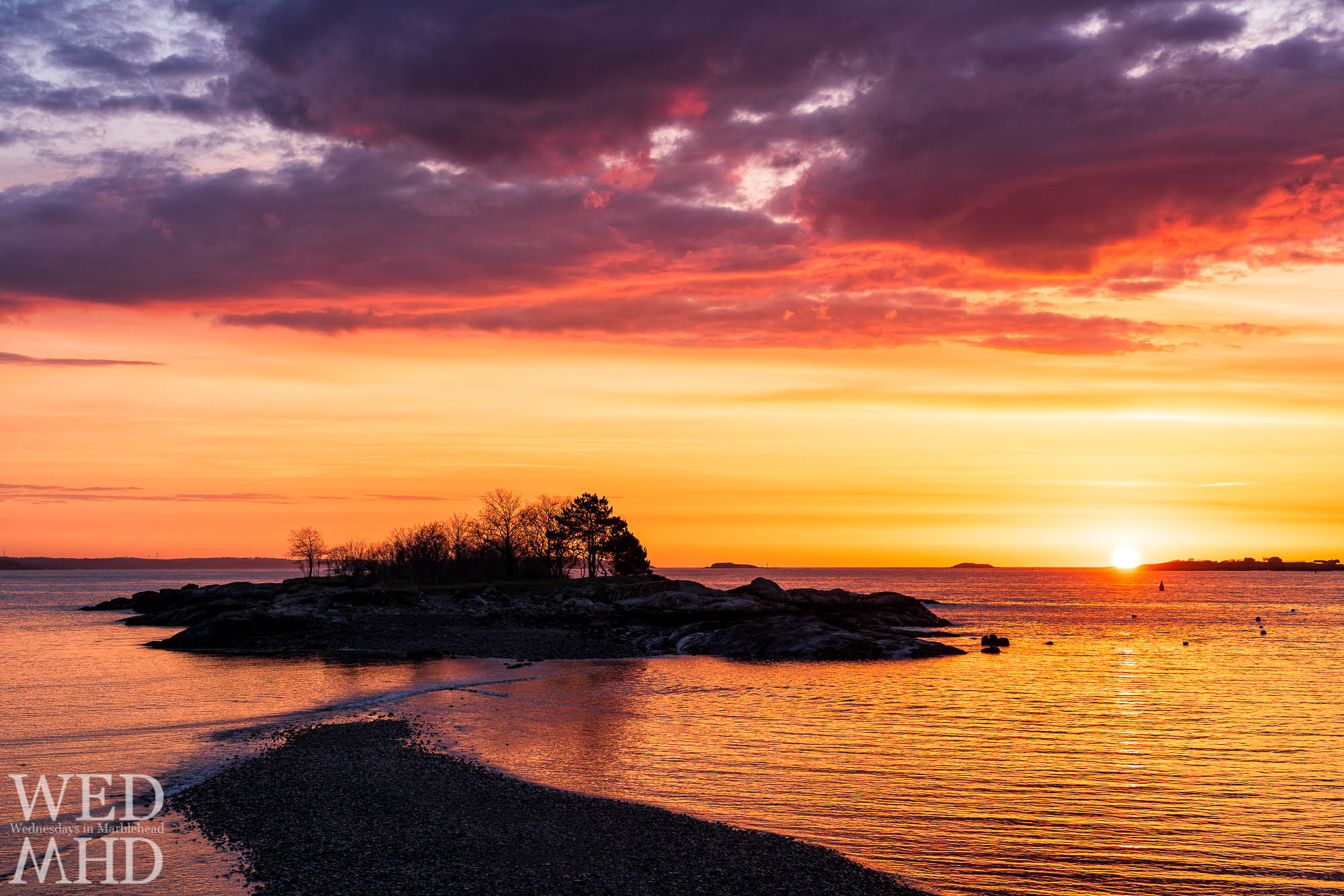 A mid-April sunrise over Gerry Island colors the sky in orange and pink which reflects in the calm water