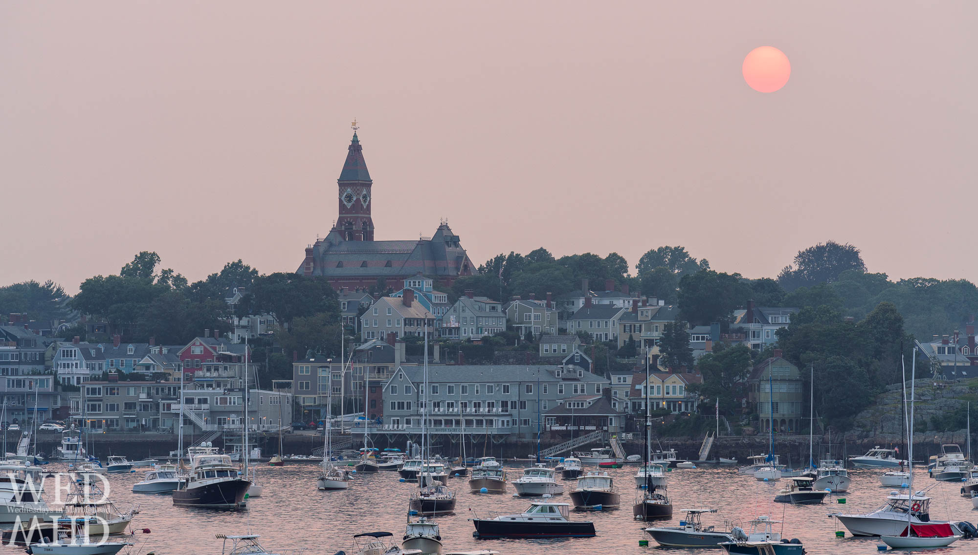 Smoke from fires on the West Coast created conditions for a red sun to set over Abbot Hall and Marblehead harbor
