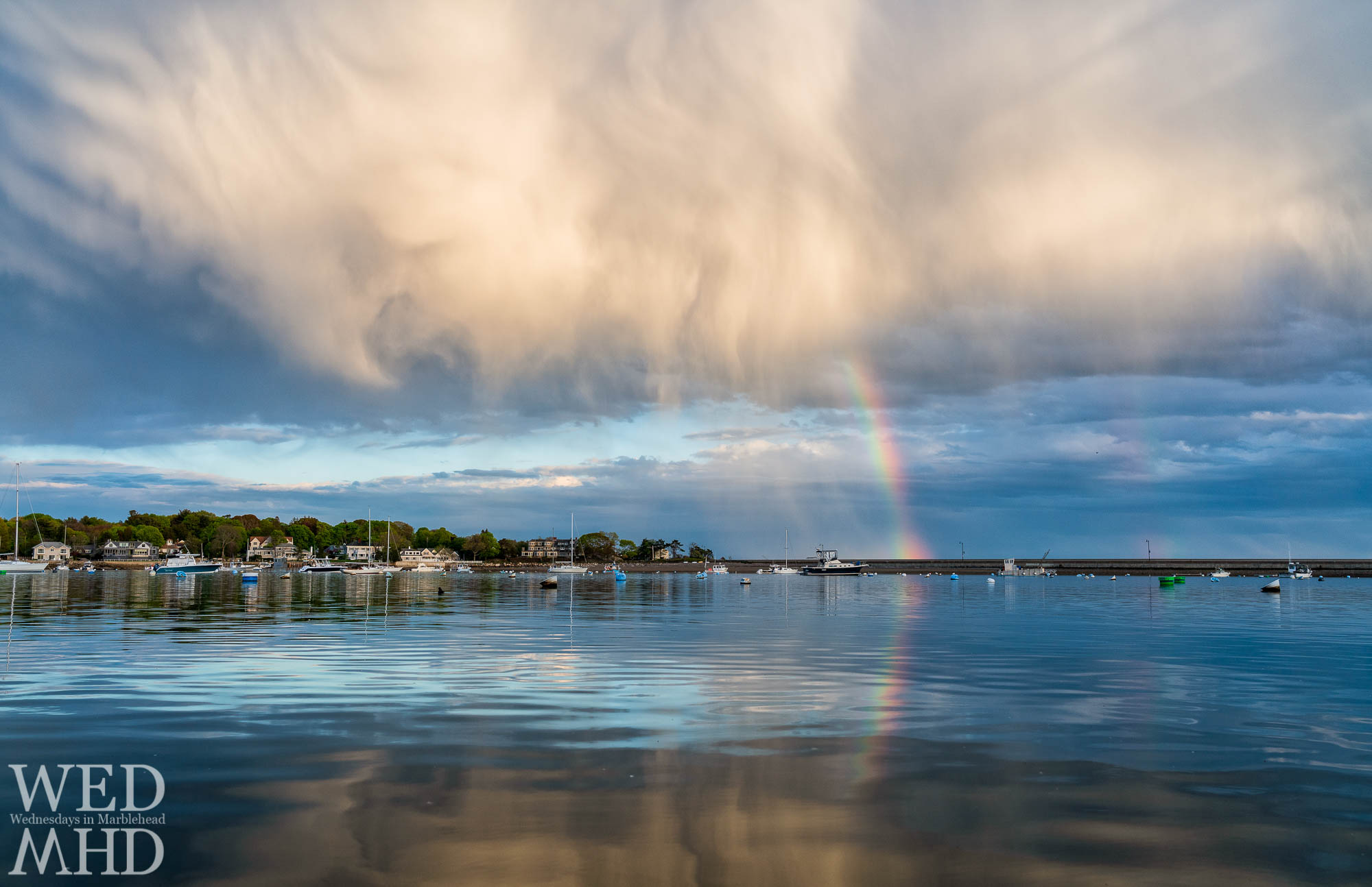 A hint of a double rainbow and great clouds make for a memorable scene in this low angled shot meant to accentuate the reflections
