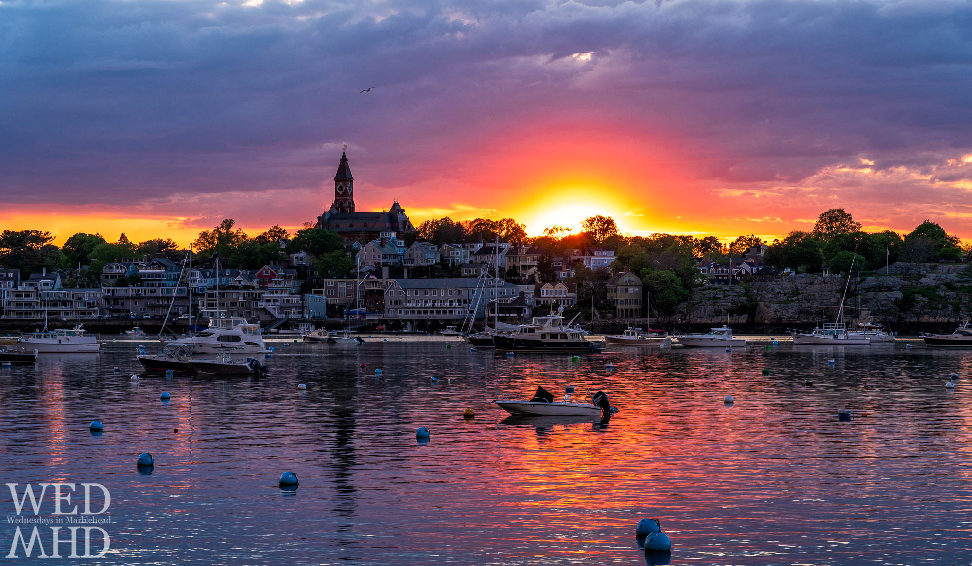 Sunset light erupts beside Abbot Hall on a mid-May evening with few boats in the harbor and a seagull flying overhead