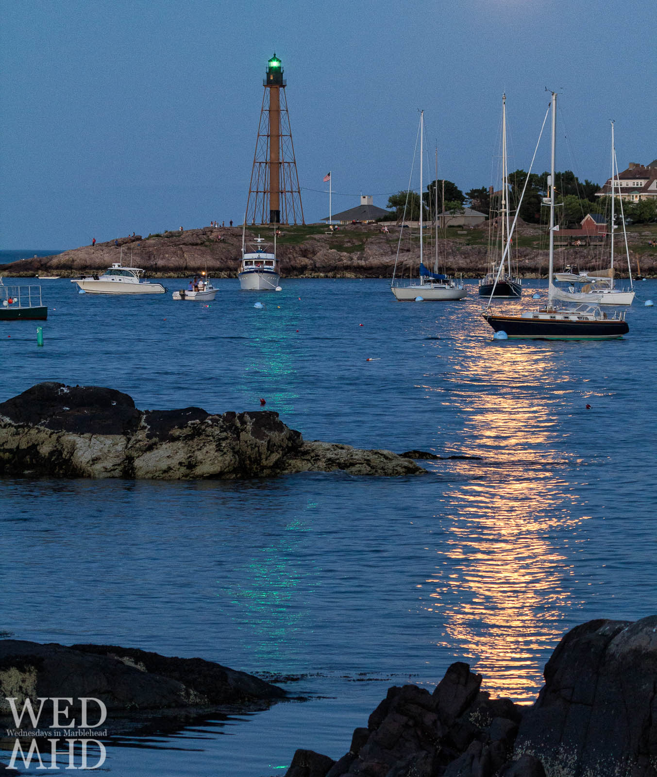 The golden glow from a risen moon casts its light alongside the green of Marblehead Light