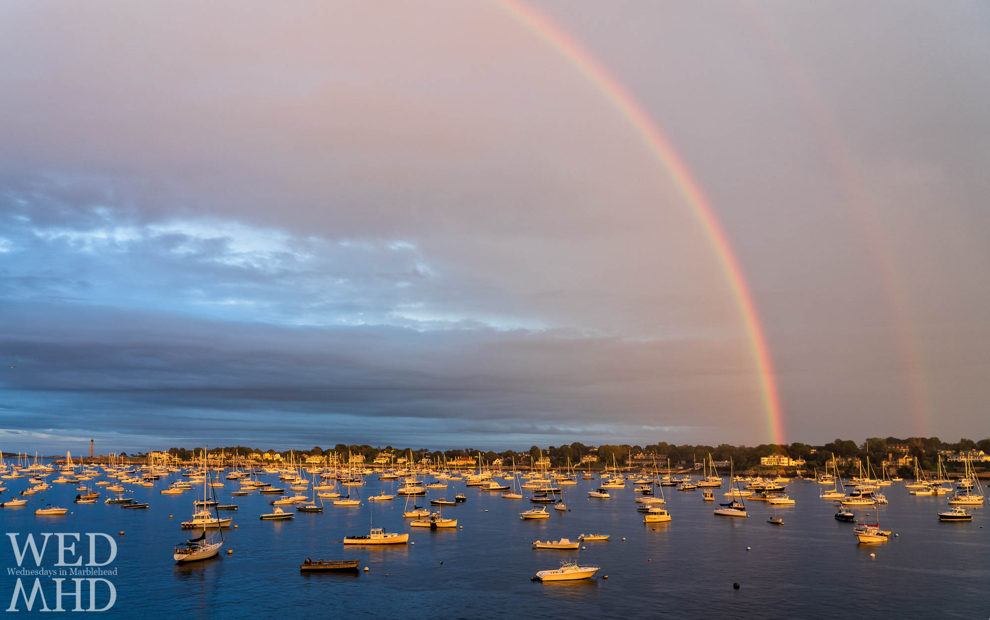 A rainbow appears as a light after the storm passes by Marblehead Harbor on a fall evening with boats filling the moorings