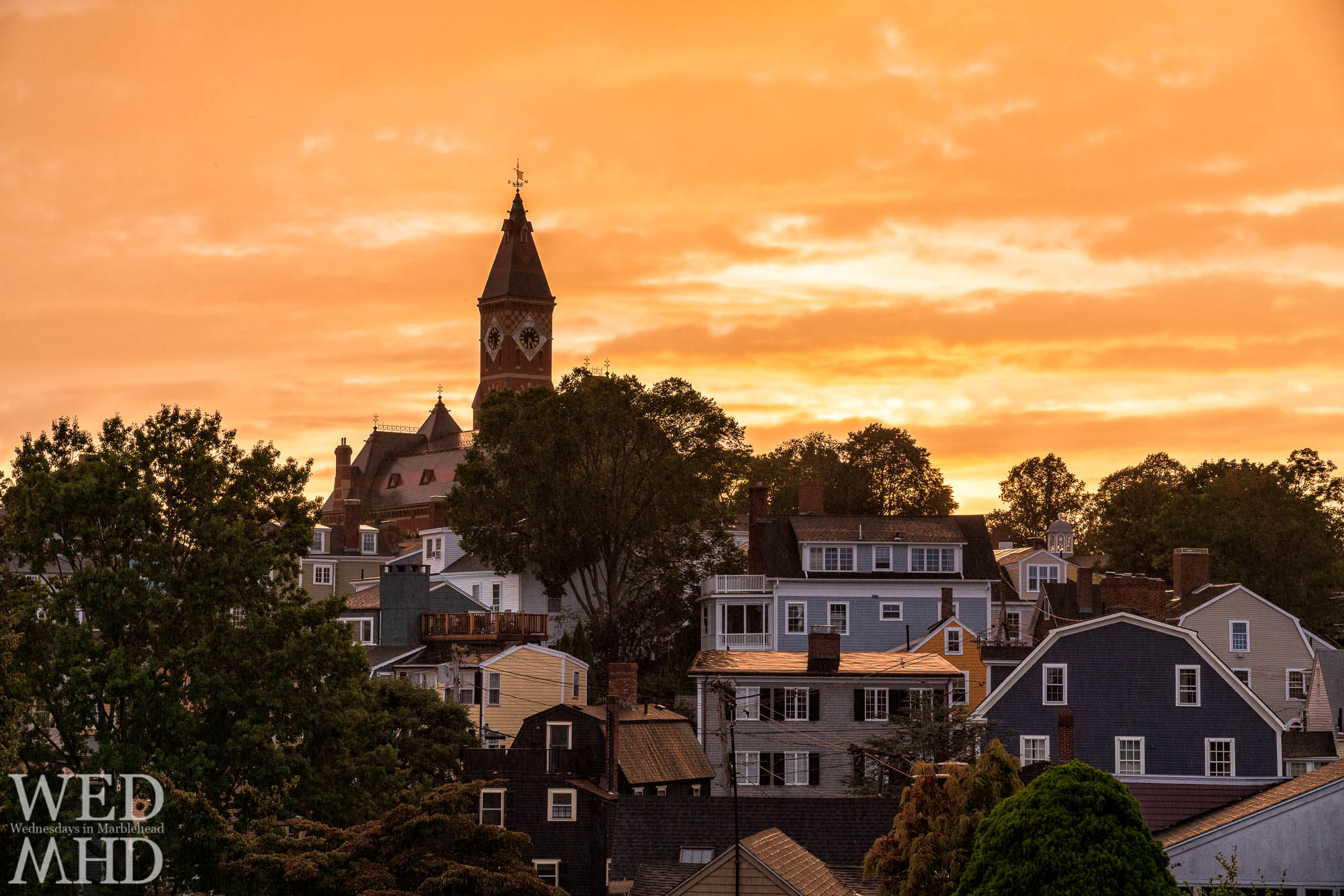 The view of Abbot Hall from Crocker Park amidst a sunset in the rain features golden light surrounding the building and its neighboring homes