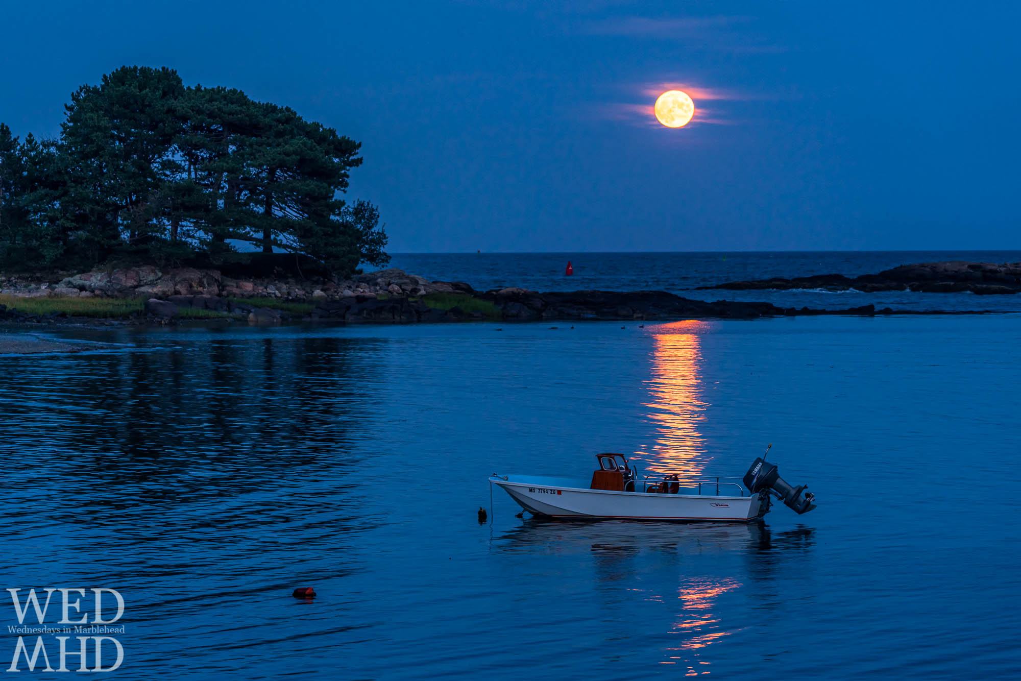 A whaler is caught in the wake of the full moon rising over Brown's Island