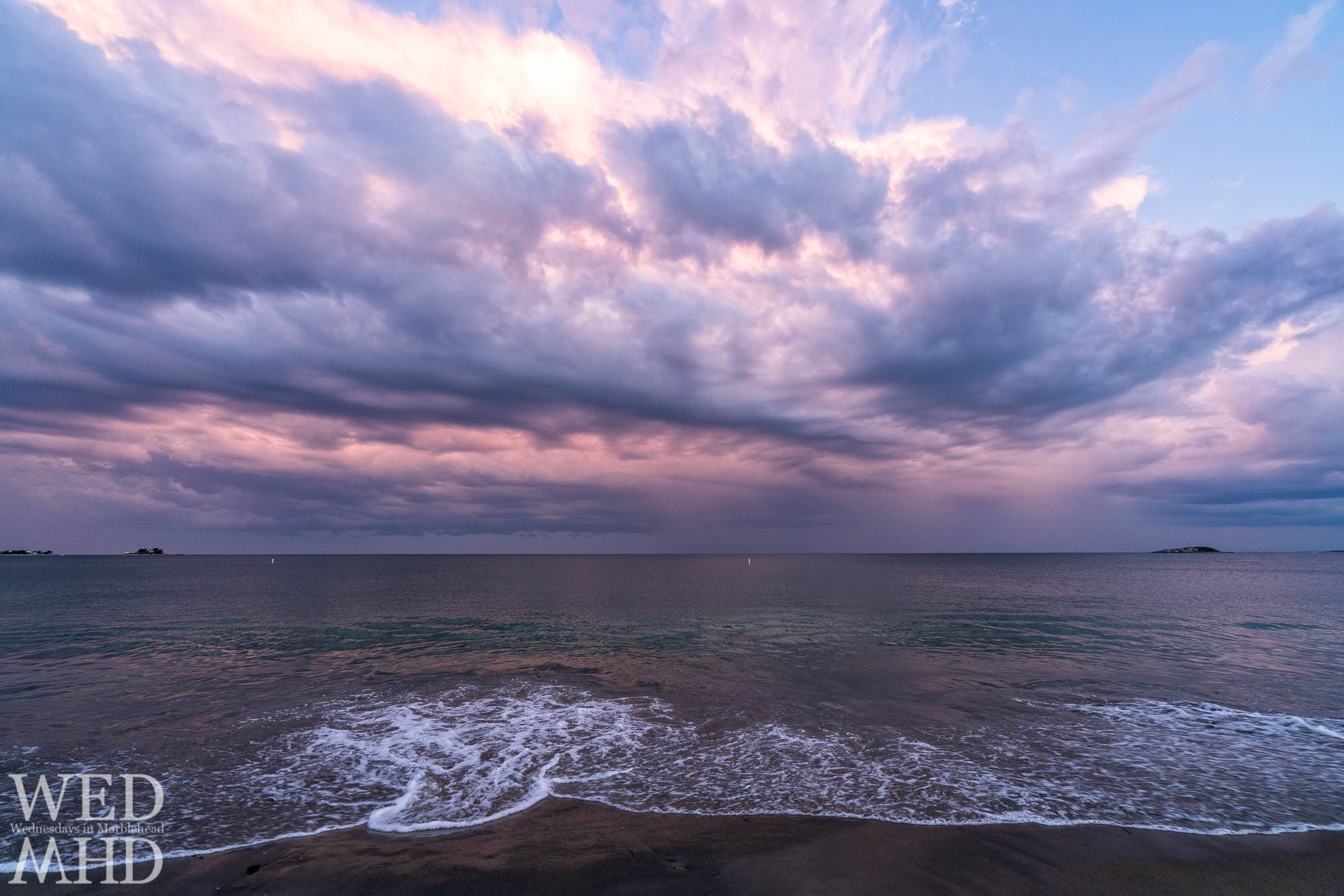 White foam comes ashore on a calm evening in Marblehead with purple light shining overhead at Devereux Beach