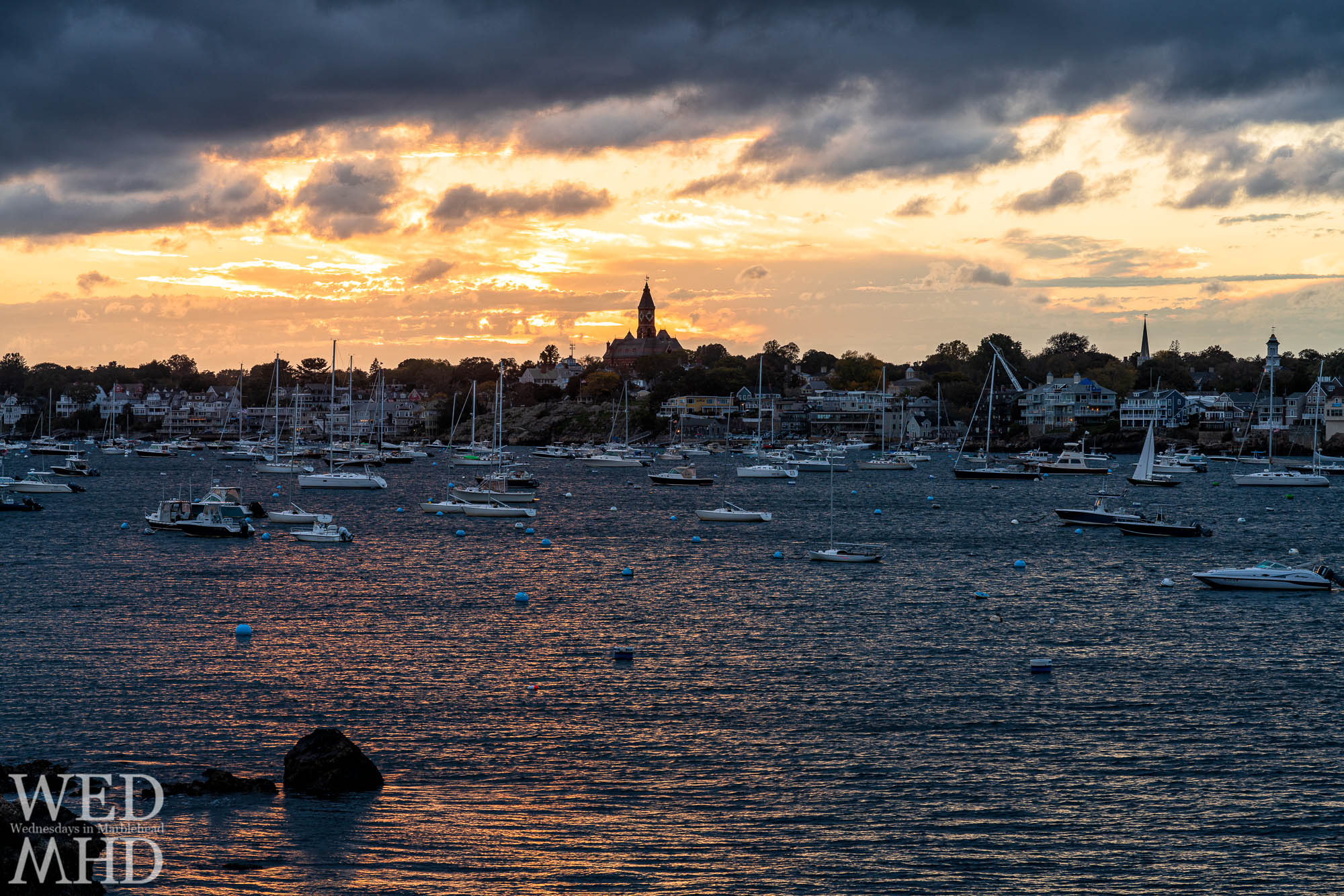 A hint of sunset shines over Abbot Hall and sets a glow on the harbor with a lone rock casting shadows on the water